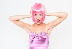在白色背景桃红色假发的滑稽的少妇和摆在惊奇的 免版税库存图片