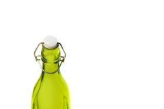 在白色背景橄榄油隔绝的老绿色玻璃瓶 在瓶脖子的白色塑料黄柏和一层生锈的门闩 免版税图库摄影