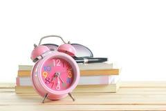在白色背景的一张木桌安置的桃红色闹钟 库存图片