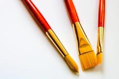 在白色背景的三支金黄刺毛画笔与拷贝空间 免版税库存照片