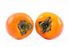 在白色背景的两个橙色柿子 免版税库存照片