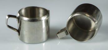 在白色背景的两个金属镀镍层的杯子 库存照片