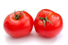 在白色背景的两个整个蕃茄 免版税库存图片