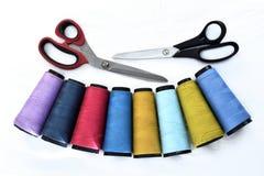 在白色背景的五颜六色的缝合针线卷轴与剪刀 库存照片