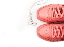 在白色背景的体育桃红色运动鞋与耳机 培训 体育运动 图库摄影