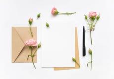 在白色背景的信件和eco纸信封 邀请卡片或者情书与桃红色玫瑰 假日概念,顶视图, fl 免版税库存照片