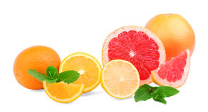 在白色背景的可口citruces 甜点切了桔子、柠檬和葡萄柚用绿色薄菏 图库摄影