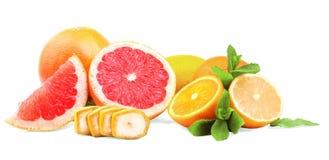 在白色背景的各种各样的柑橘 水多的桔子、柠檬和葡萄柚 一个切的香蕉和薄荷叶子 库存图片