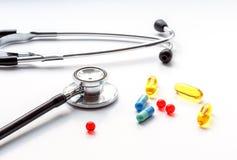 在白色背景的听诊器与混合药片 免版税库存照片