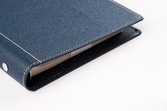 在白色背景的壁角深蓝色的组织者书 免版税库存照片