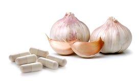 在白色背景的大蒜和药片胶囊 免版税库存图片