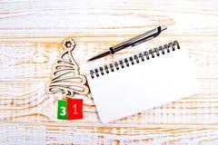 在白色背景的天31th月,日历与木圣诞树,笔和笔记本 免版税库存图片
