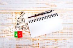 在白色背景的天31th月,日历与木圣诞树,笔和笔记本 图库摄影