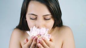 在白色背景的年轻女人嗅到的花 影视素材