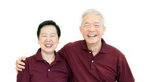 在白色背景的愉快的亚洲资深夫妇爱并且拥抱 免版税库存照片