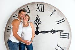 在白色背景的愉快的怀孕的夫妇与巨型时钟 免版税库存照片