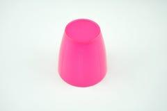 在白色背景的桃红色塑料杯子 免版税库存照片