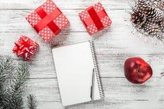 在白色背景的现代礼物安排和白色留言簿、圣诞卡和其他寒假,礼物 库存照片