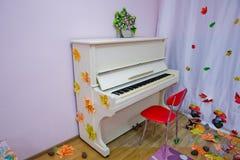 在白色背景的白色大平台钢琴 戏剧音乐 有专栏的绝尘室和关于墙壁的钢琴 在黑暗的白色钢琴 免版税库存照片