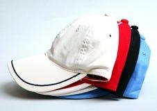 在白色背景的白色,黑,红色和蓝色棒球帽 库存图片