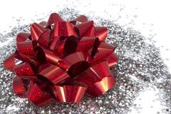 在白色背景的红色礼物弓与银色闪烁 免版税库存图片