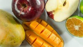 在白色背景的红色苹果芒果蜜桔 库存照片
