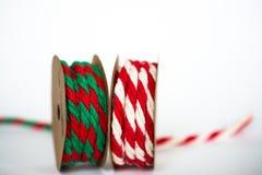在白色背景的红色/白色和红色/绿色麻线丝带 图库摄影