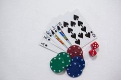 在白色背景的纸牌、模子和赌博娱乐场芯片 免版税图库摄影