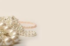 在白色背景的美丽的奶油色婚礼珍珠项链 免版税库存照片