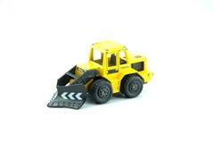 在白色背景的老黄色拖拉机玩具 免版税库存照片