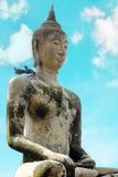 在白色背景的菩萨雕象与在他的肩膀、清楚的天空和白色云彩的两只鸟 免版税库存图片