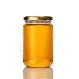 在白色背景的蜂蜜瓶子 免版税图库摄影