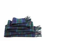 在白色背景的被折叠的温暖的绿色蓝色羊毛围巾 库存照片