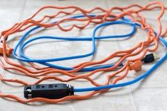 在白色背景的被缠结的蓝色和橙色延长绳路 库存照片