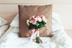在白色背景的豪华婚礼花束在棕色枕头 免版税库存照片