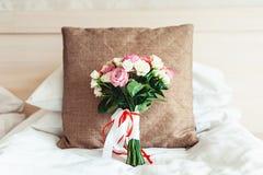 在白色背景的豪华婚礼花束在棕色枕头 库存图片