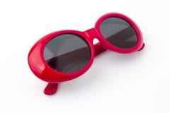 在白色背景的逗人喜爱的红色圆的太阳镜 免版税库存照片