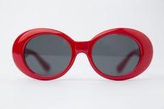 在白色背景的逗人喜爱的红色圆的太阳镜 图库摄影