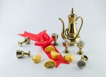 在白色背景的金锭红色丝带弓金水罐茶玻璃 库存照片