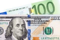 在白色背景的钞票100欧洲和美元 免版税库存图片