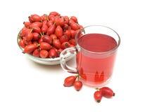 在白色背景的饮料和野玫瑰果莓果 库存图片