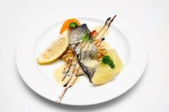 在白色背景的鱼可口板材 免版税库存照片