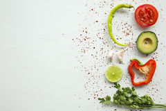 在白色背景的鳄梨调味酱捣碎的鳄梨酱成份:鲕梨,辣椒粉,蕃茄,葱 免版税库存照片