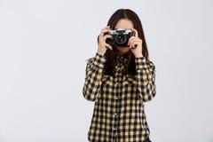 在白色背景的年轻美丽的深色的摄影师 免版税图库摄影