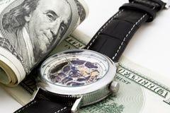 在白色背景的100美元与手表 免版税库存图片