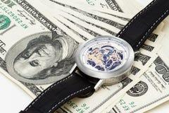 在白色背景的100美元与手表 库存图片