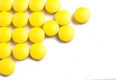 在白色背景的黄色药片 免版税库存照片