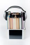 在白色背景的Audiobook 耳机投入了在堆五颜六色的书,空的盖子,广告文本的拷贝空间 免版税库存图片