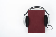 在白色背景的Audiobook 耳机投入了在红色精装书书,空的盖子,广告文本的拷贝空间 距离 免版税图库摄影