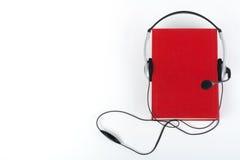 在白色背景的Audiobook 耳机投入了在红色精装书书,空的盖子,广告文本的拷贝空间 距离 免版税库存照片
